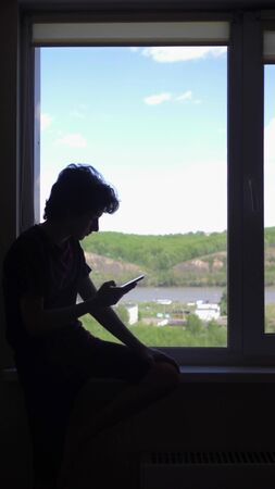 vertical. silhouette. The boy uses a phone, by the window against the blue sky