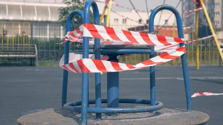 Empty playground during the coronavirus pandemic. warning tapes on the rides