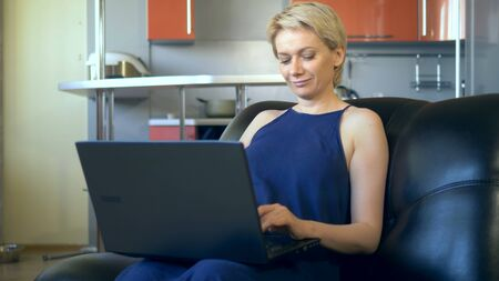 beautiful young woman uses laptop sitting in a chair in the kitchen