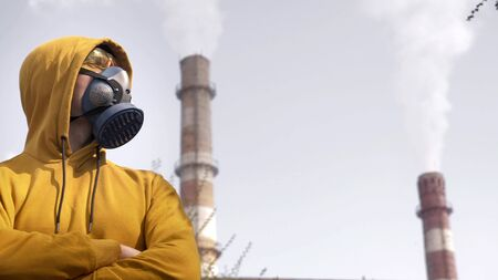 man in respirator against the background of factory chimneys