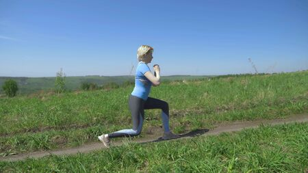 slender woman goes in for sports in a field on the hills. makes lunges