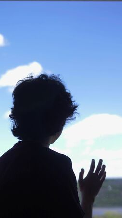 vertically. silhouette. teenager sits on a windowsill against a blue sky