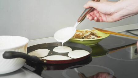close up, someone is cooking pancakes in a pan on a touch stove