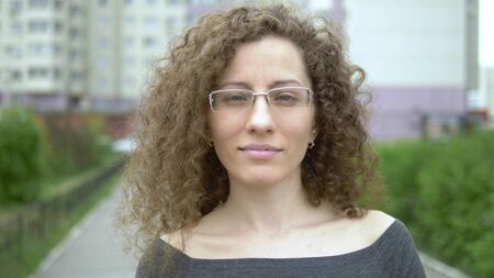 beautiful smiling woman in glasses with curly hair walks on a city street. Zdjęcie Seryjne
