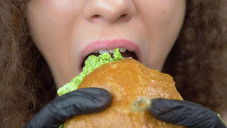 closeup of the lips. woman eats a juicy hamburger, hands in black rubber gloves