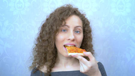portrait. woman bites off a piece of pizza with a smile