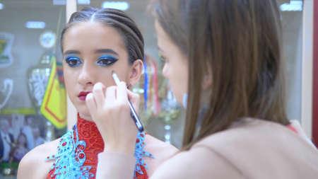 close-up. portrait of a beautiful girl model. makeup artist makes bright makeup