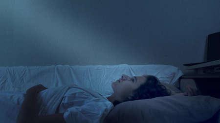 teenage boy suffering from insomnia lying in bed at night Reklamní fotografie