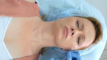 woman takes injections in the face at the reception at the beautician Stock fotó