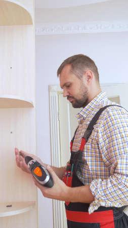 Young male furniture assembler assembles a built-in wardrobe 版權商用圖片