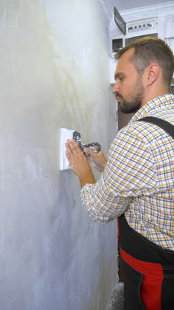 young handsome male builder lays plaster on the wall with a trowel. home repairs