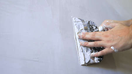 close-up of a hand. a man applies plaster with a trowel to the wall