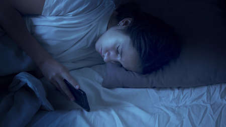 teen girl using smartphone while lying in bed at night