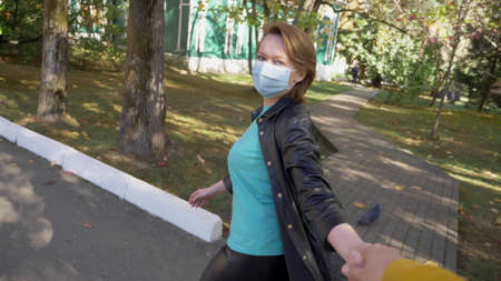 first-person view, a woman in a medical mask leads a man by the hand 版權商用圖片