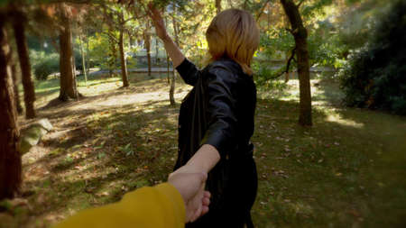 Follow me. a woman leads a man by the hand in the park. first-person view 版權商用圖片