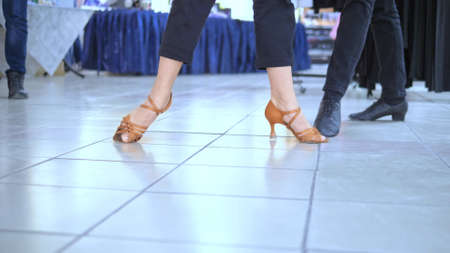 feet of ballroom dancers in casual clothes and professional shoes