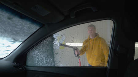 view from inside the car. a man washing a car at a car wash