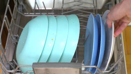 close-up of hands. woman puts dishes in the dishwasher
