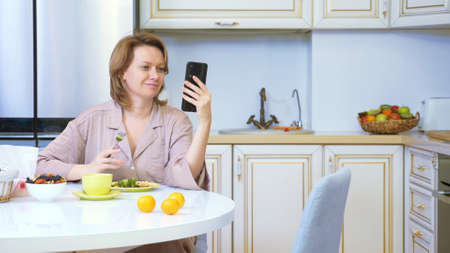 woman eating while sitting in the kitchen at the table and using her smartphone