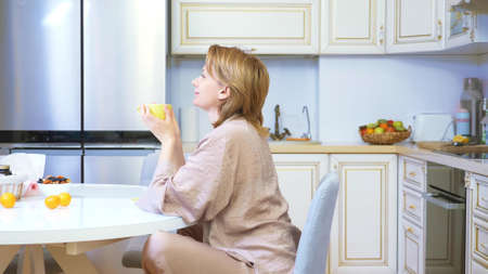 smiling, dreaming woman drinking tea at home in her kitchen
