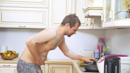 hungry bare chested man checks the pan on the stove