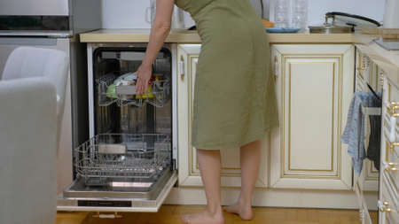 woman loading dishes into the dishwasher at home in her kitchen