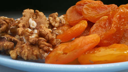extremely close-up, detailed. walnut kernels and dried apricots on a blue plate