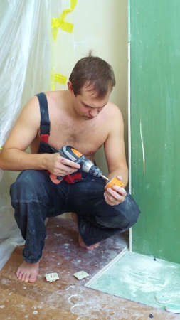 a man in overalls inserts a socket into the wall with a screwdriver