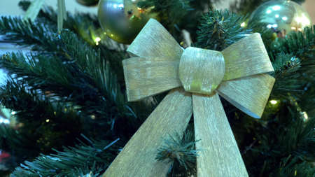 close-up of golden bow on christmas tree with glowing garlands
