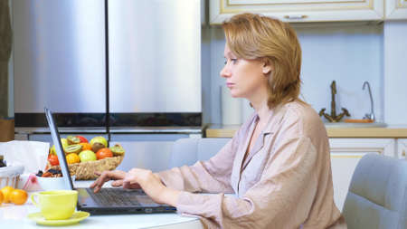 beautiful woman working on laptop while sitting at home in the kitchen