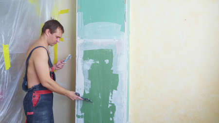 a man in overalls applies plaster with a spatula to the wall