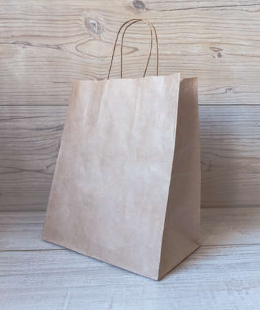 Mokeup of a craft paper shopping bag with handles on the wooden background.