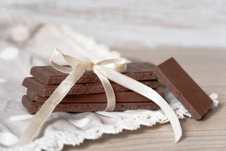 Elegant composition of milk chocolate with a ribbon and a bow on the tablecloth. Stok Fotoğraf - 125821823