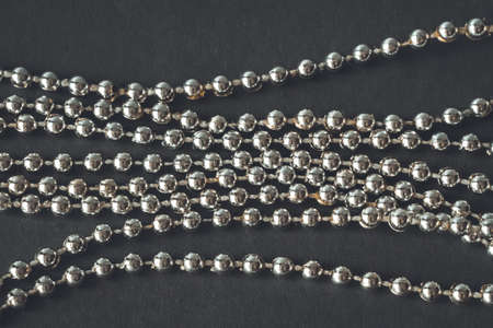 Close-up of silver beads garland on black background.