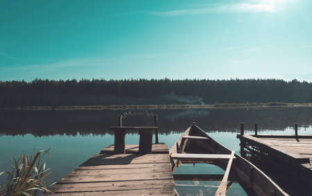 Scenic landscape view with tranquil lake, idyllic piers and boat in the morning.