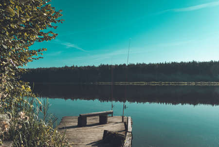 Atmospheric autumn photo. Scenic landscape view with tranquil lake, idyllic pier and fishing rods.