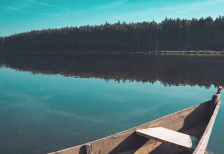 Atmospheric moody photo. Scenic landscape view with forest, tranquil lake and fishing boat. Фото со стока