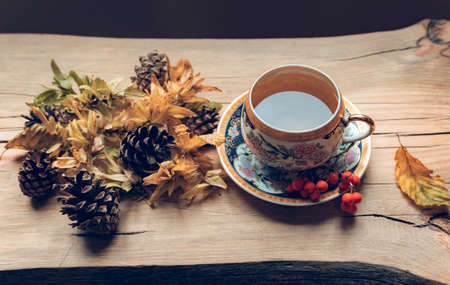 Autumn composition with tea on wooden background. Cozy autumn background.