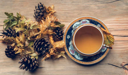 Autumn composition with tea on wooden background. Cozy fall background.