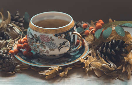 Autumn composition with tea on wooden background. Cozy fall background. Fall vibes.