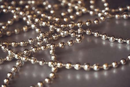 Close-up of golden shiny beads garland on grey background. Decorative background.