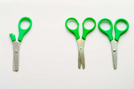 Two pair of normal scissors stood away from one handicap photo