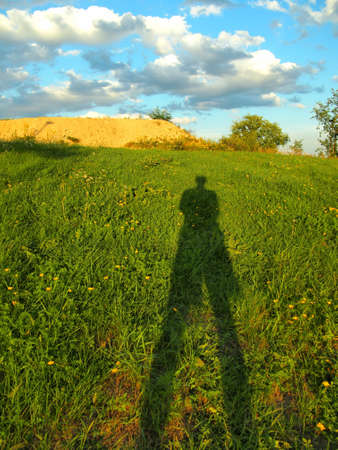 Man shadow on a grass field