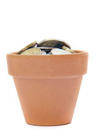 olla barro: una olla de barro con una sola moneda en el interior Foto de archivo