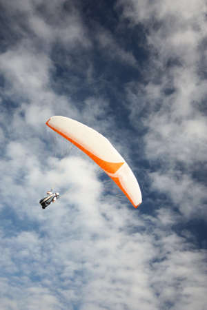 gliding: a single person parasailing  with lots of clouds in background