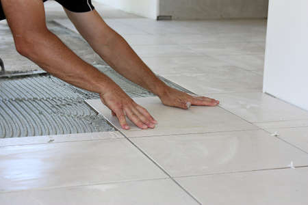 lying on floor: a male tiler laying light color floor tiles Stock Photo