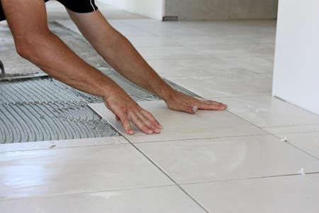 ceramics: un piastrellista maschio posa piastrelle di colore chiaro