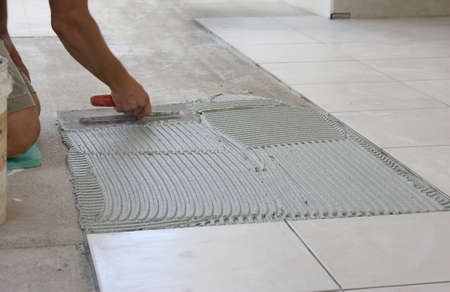 a young male tiler tiling the floor photo
