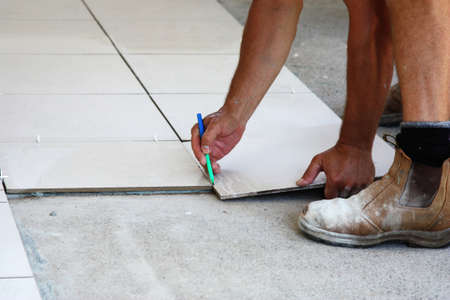 a male tile laying floor tiles on a home photo