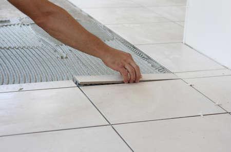 a tiler laying a new tiles to an outdoor patio
